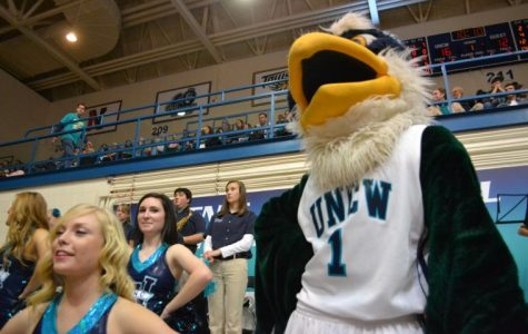 Sammy the Seahawk watches from the sidelines as the UNCW men's basketball team pushes past the Northeastern Huskies. Sammy not only serves as a symbol of UNCW, but he also serves as the physical embodyment of school spirit and the campus and community coming together to cheer on our Boys in Teal.