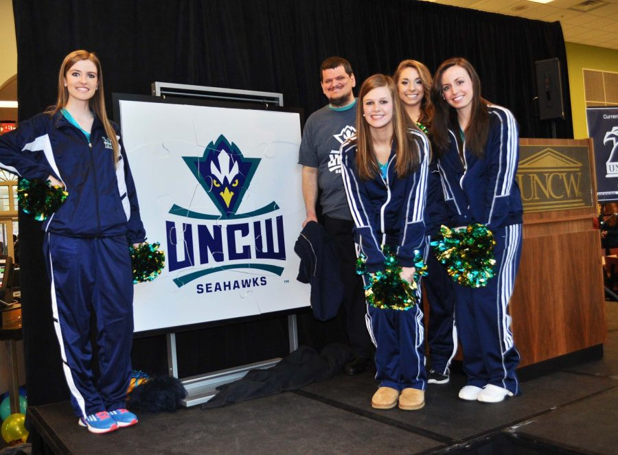 Some members of UNCW's cheer team pose next to the new, unveiled logo. The logo was released right before the UNCW vs. Elon basketball game where students cheered the Seahawks on to victory at Trask Coliseum.