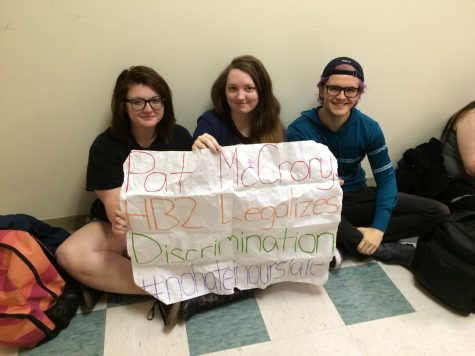 UNCW student protesters hold up homemade signs at the UNC system-wide bathroom sit-in against controversial House Bill 2.