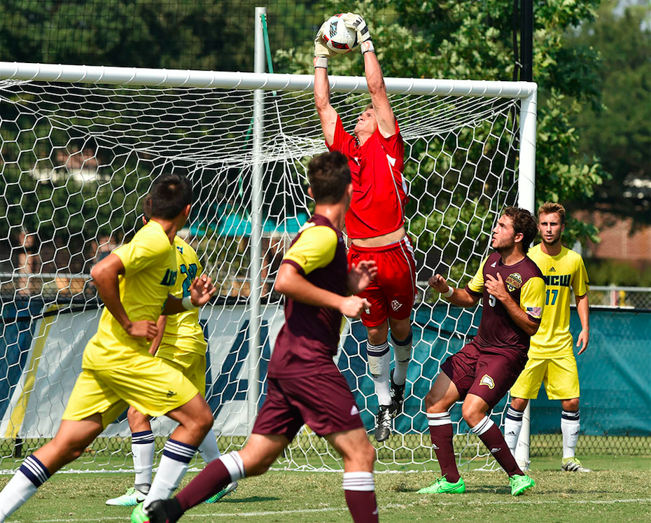 Ryan Cretens, in red, reaches up to save a shot sent by Winthrop late in Sunday's match.