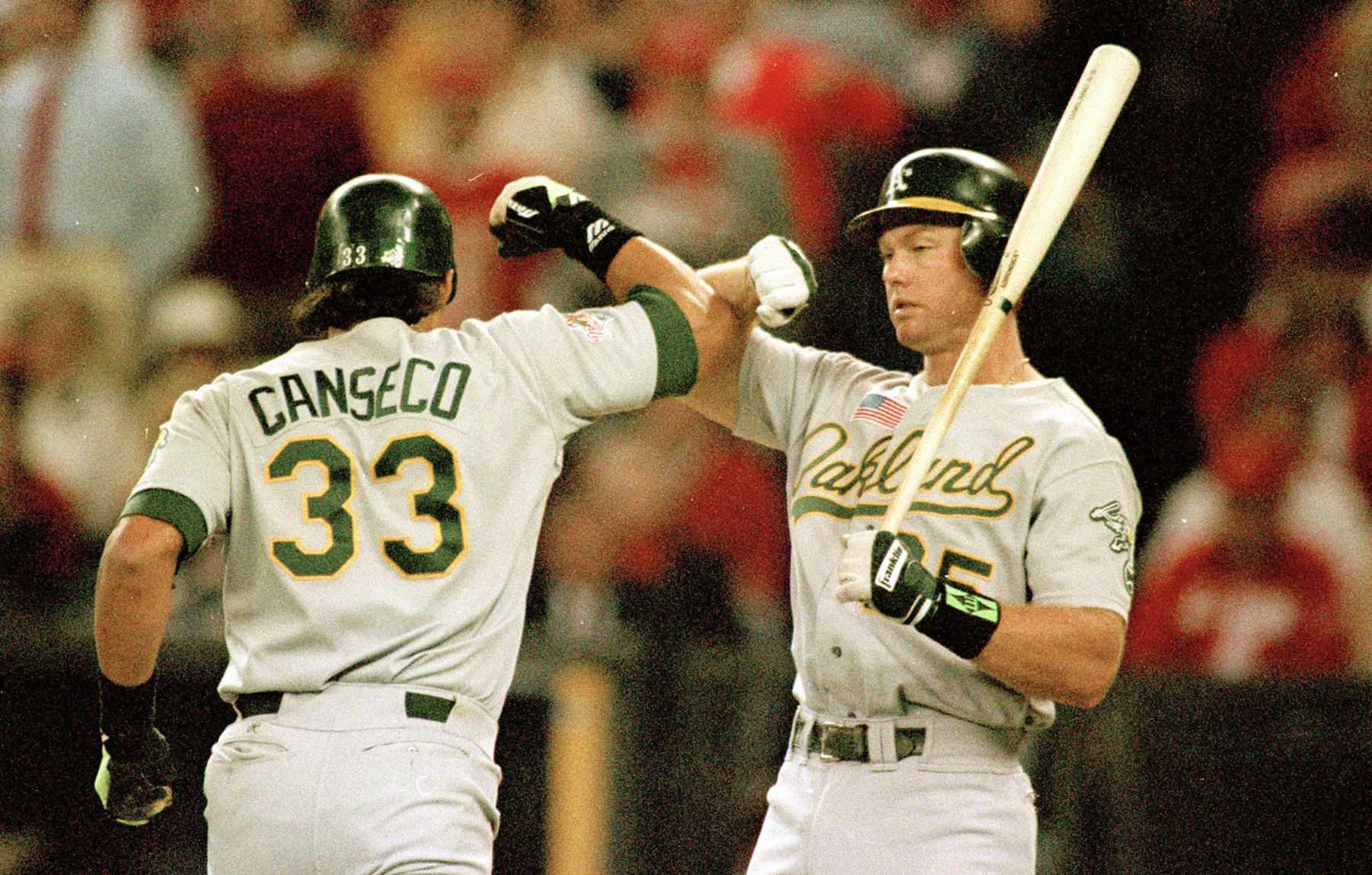 Jose Canseco, left, and teammate Mark McGwire exchange their