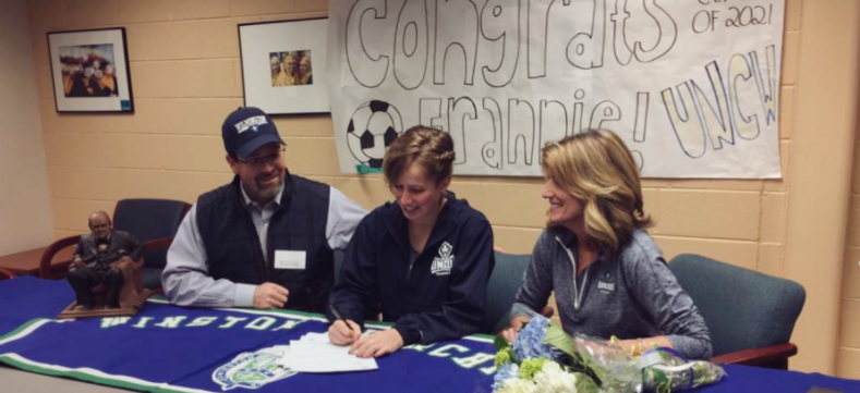 Francine Phillips, one of 12 recruits to commit to UNCW women's soccer on Feb. 1, signs her National Letter of Intent.