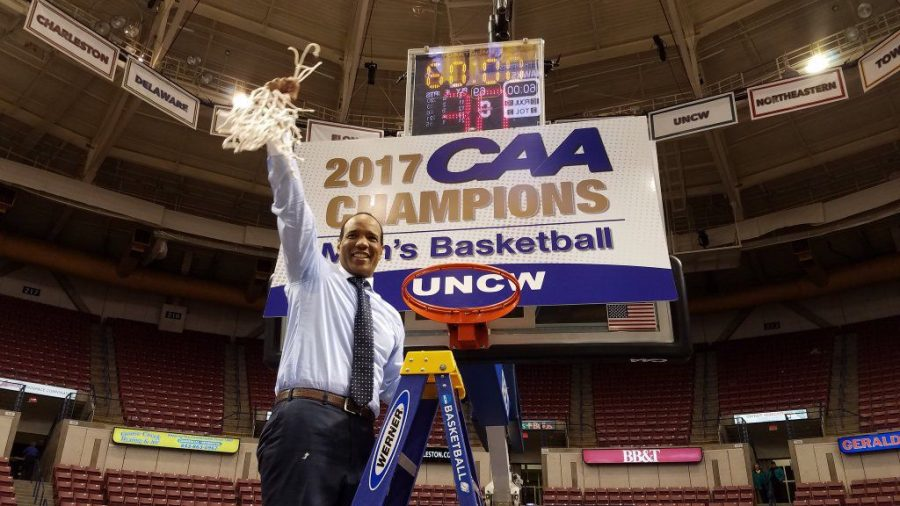 Kevin+Keatts%2C+head+coach+of+the+UNCW+Seahawks%2C+raises+the+game+net+over+his+head+after+winning+a+second+consecutive+CAA+tournament+title.