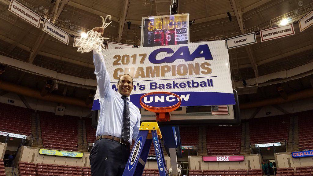 Kevin Keatts, head coach of the UNCW Seahawks, raises the game net over his head after winning a second consecutive CAA tournament title.