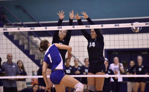 Madison Peters, left, and Sydney Brock, right, block a spike attempt from a Barton player in UNCW's exhibition game vs. Barton College on Aug. 20.