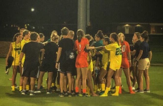 Members of the UNCW and Virginia women's soccer teams gather for a postgame huddle on Friday, Aug. 18.