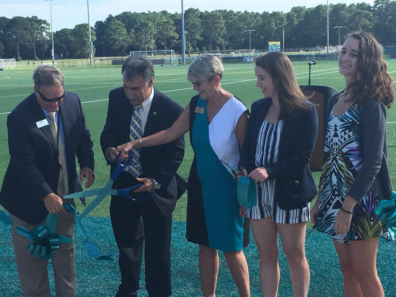UNCW Chancellor Jose V. Sartartelli, center-left, cuts the ribbon during the grand-opening ceremony for the university's recreational fields.