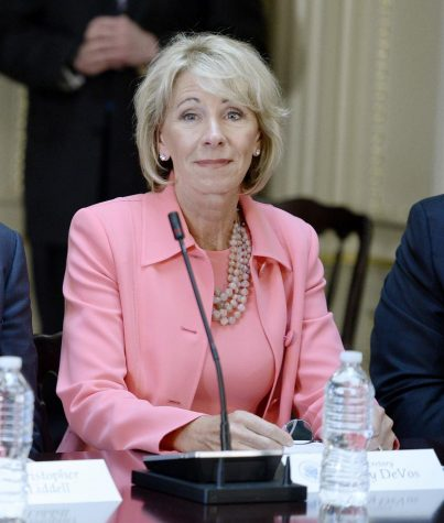 Education Sec. Betsy DeVos listens as U.S. President Donald Trump speaks during a strategic and policy discussion with CEOs in the State Department Library in the Eisenhower Executive Office Building on April 11, 2017, in Washington, D.C. DeVos has rescinded Obama-era guidelines on campus sexual assault. (Olivier Douliery/Abaca Press/TNS)