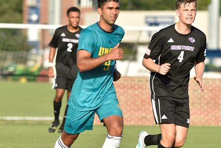 Julio Moncada, left, in UNC Wilmington's match with High Point University.