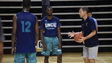 Jay Estime (12) and Ty Taylor, left, take instruction from UNCW men's basketball coach C.B. McGrath during a preseason practice.