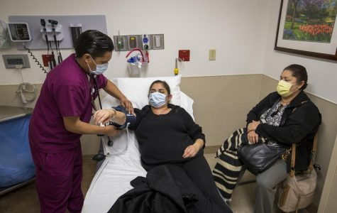 Franz Mirabal, left, patient care technician, takes the blood pressure of Adriana Gudinoperez, a patient with flu symptoms, as Carmen Perez waits with her at right in the emergency room at St. Joseph's Hospital in Orange, Calif., on Friday, Jan. 5, 2018.
