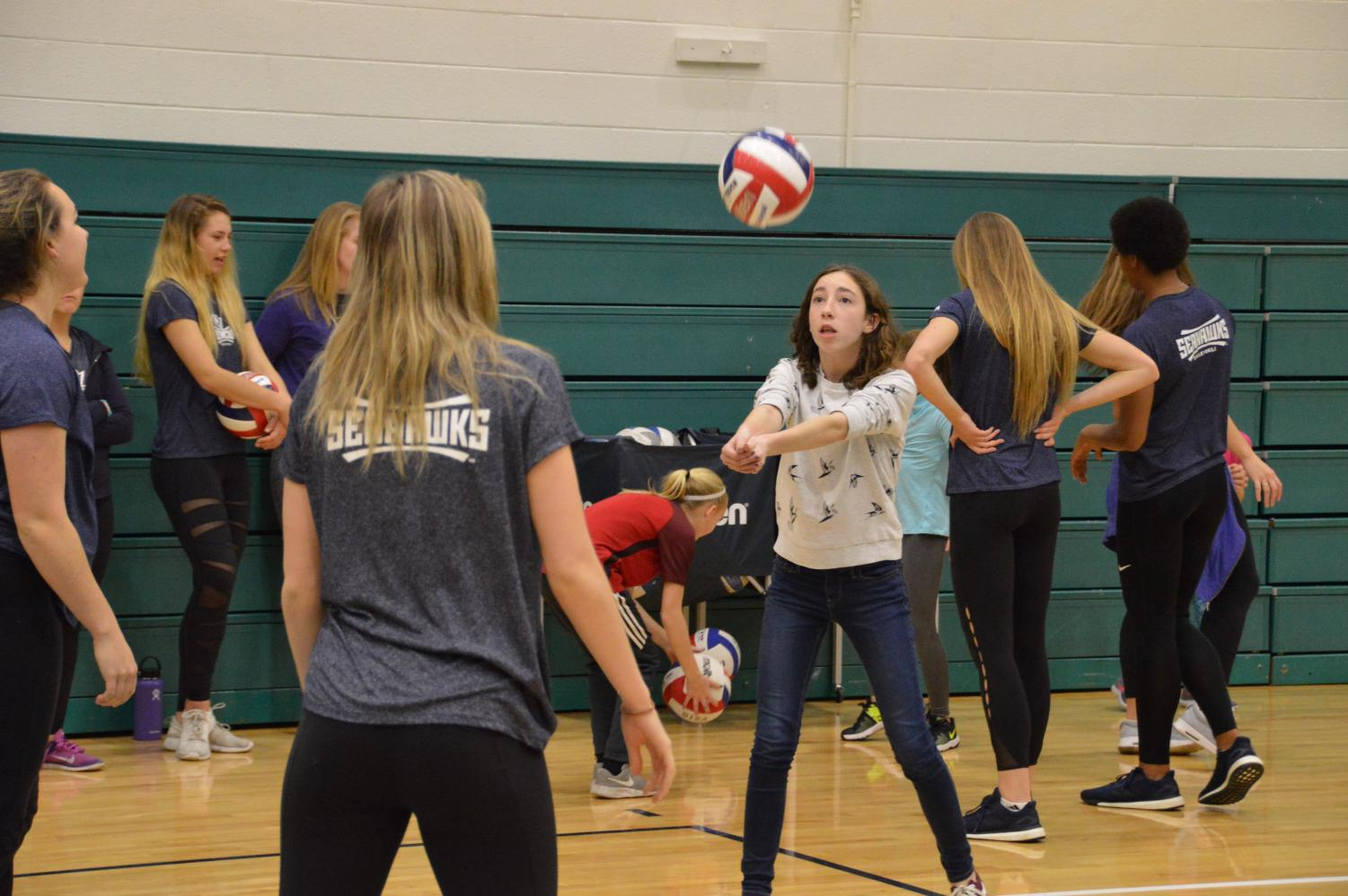 A+young+girl+works+on+volleyball+skills+with+members+of+the+team