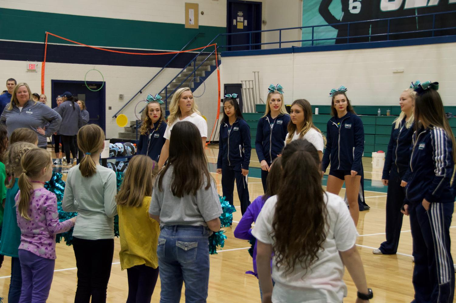 The+UNCW+Cheerleaders+teach+the+young+girls+a+cheer
