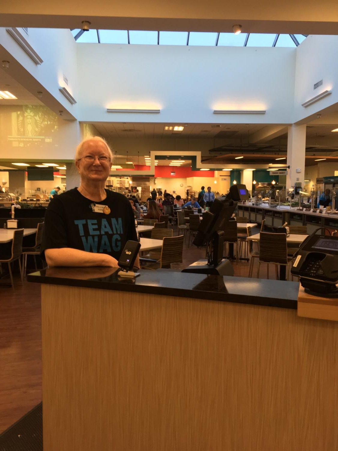 Robin, front-end cashier at Wag Hall, smiles for her final photo at UNCW (missing: her purple coat).