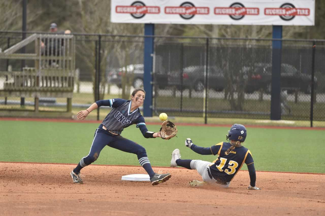 Kelsey Bryan, left, attempts to tag a runner at second base in a UNC Wilmington softball game.