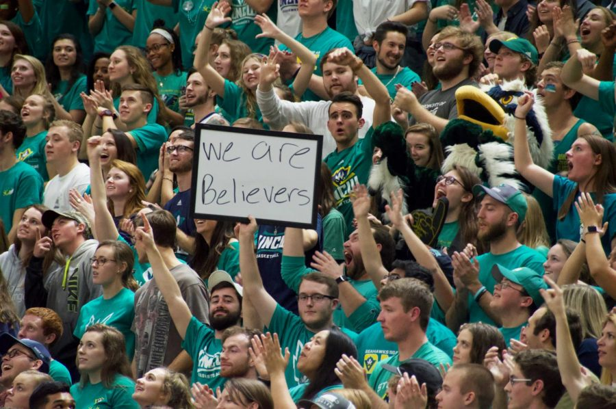 "UNC Wilmington students Brent Jansen (low, center-left) and Jacob Denton (low, center-right) hold up their signature whiteboard with the message ""We are believers"" in the student section during UNCW"