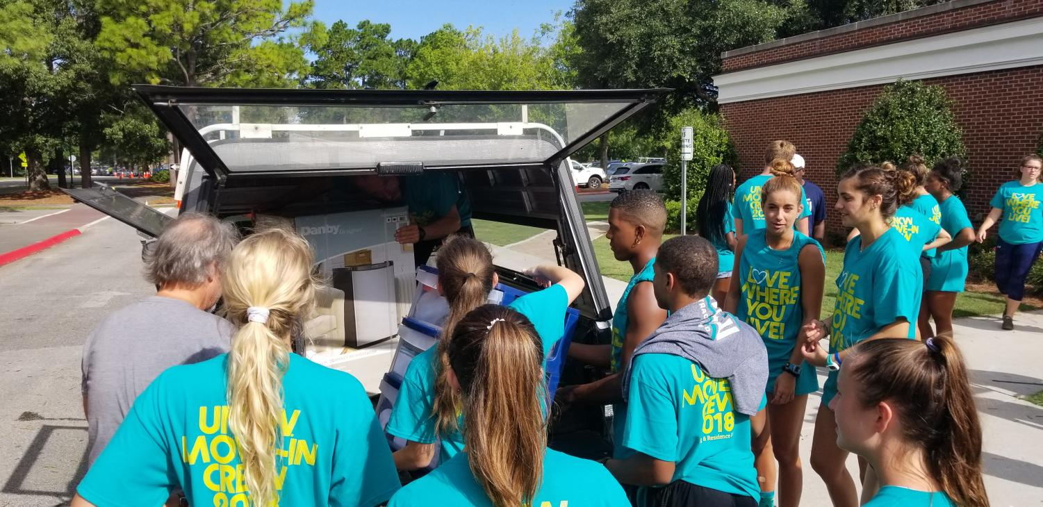 Volunteers swarm a vehicle outside Graham-Hewlett during UNCW's freshman move-in on Saturday, Aug. 18.