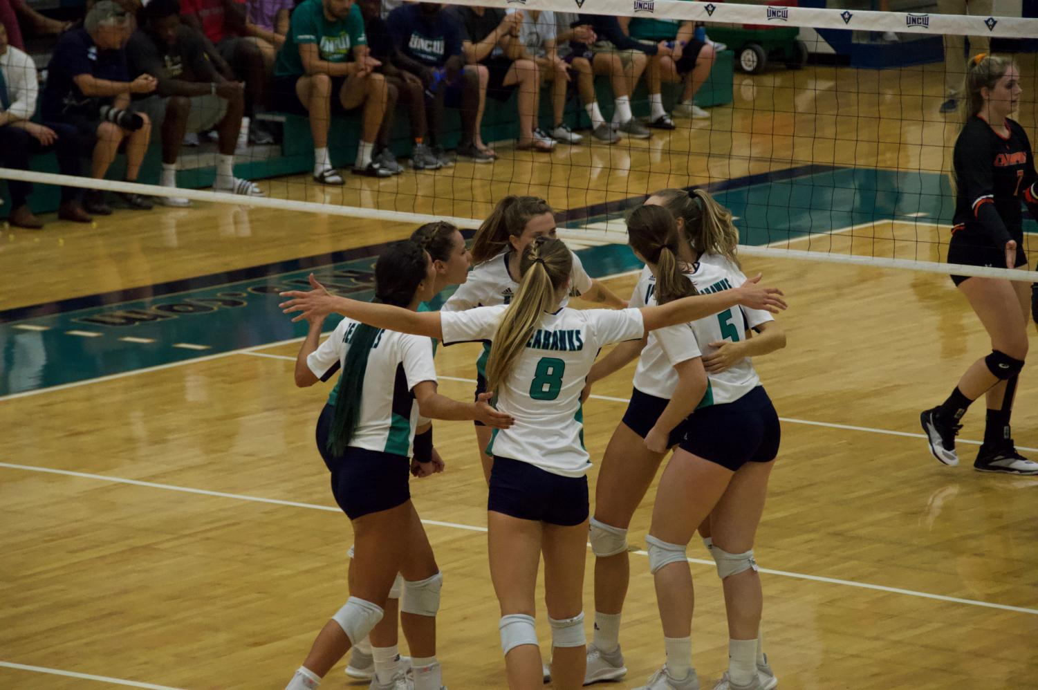 The UNCW volleyball team celebrates