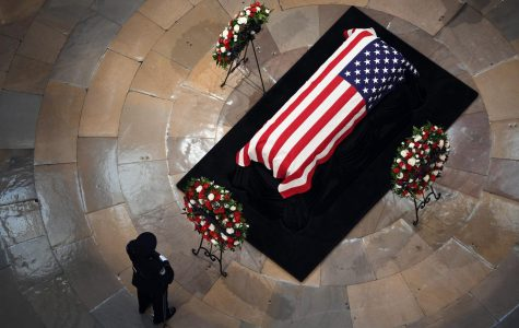 An individual pays respect near the casket of the late U.S. Sen. John McCain at the U.S. Capitol Rotunda on Aug. 31, 2018   Photo courtesy of:  (Olivier Douliery/Abaca Press/TNS)