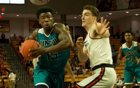 Devontae Cacok (15) drives through the lane for a layup during UNCW's season opener against Campbell.