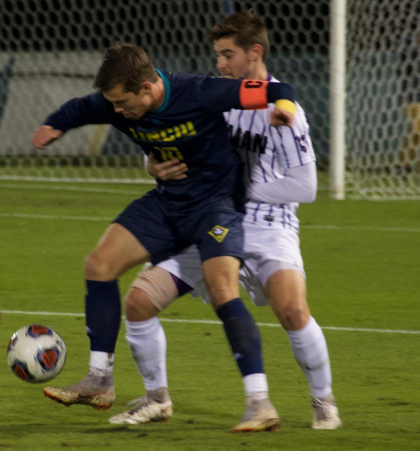 Phillip Goodrum (10) squares up with a defender during UNCW's NCAA Tournament first round match against Furman