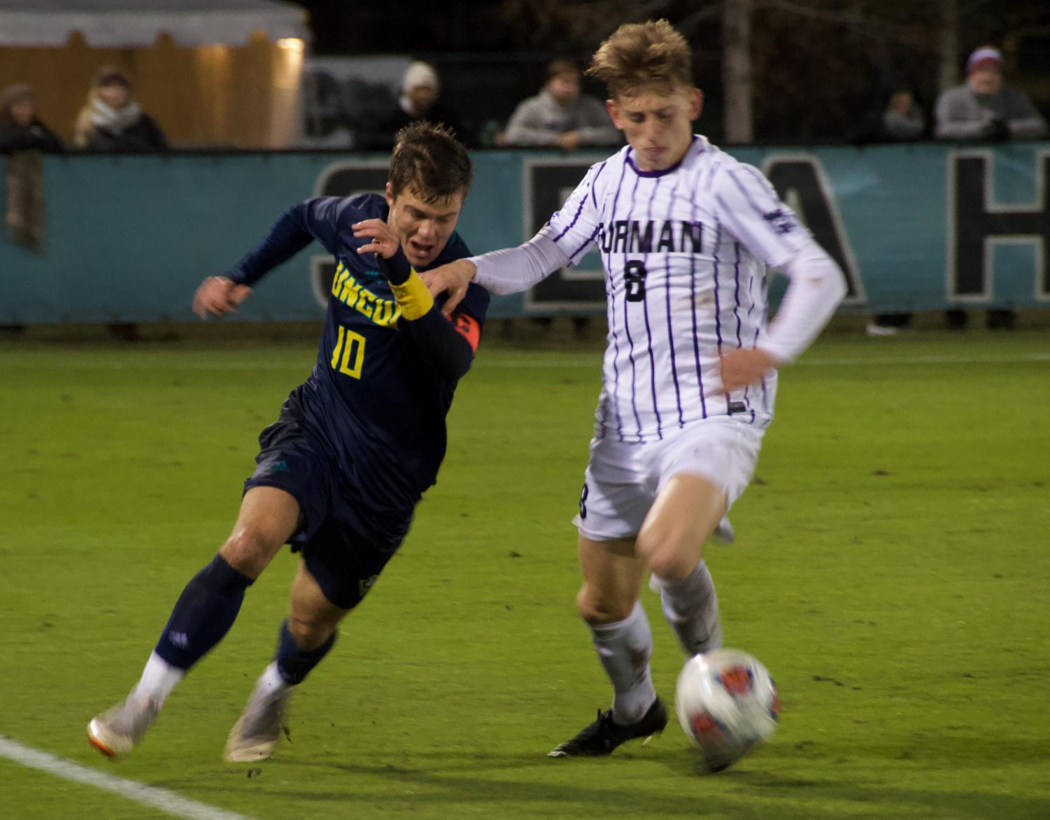 Phillip Goodrum (10) battles for the ball during UNCW's NCAA Tournament first round match against Furman