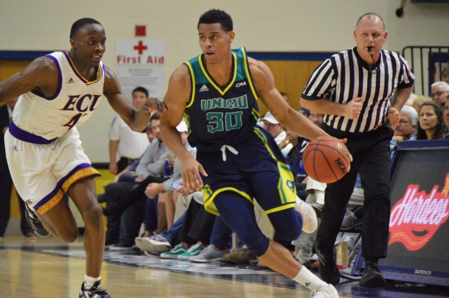 Jaylen Sims (30) dribbles up court during UNCW's 95-86 win against East Carolina on Nov. 27, 2018.