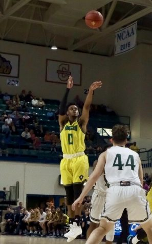 Ty Gadsden (0) takes a three-pointer during UNCW