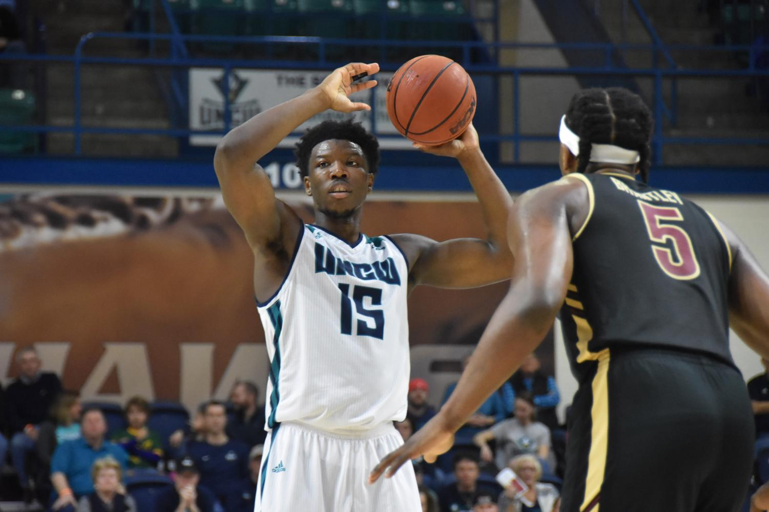 Devontae Cacok (15) looks to pass during UNCW's conference opener against College of Charleston on Dec. 29, 2018.