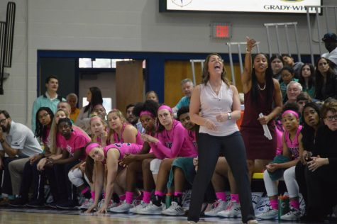 Coach Karen Barefoot celebrates alongside Seahawk's bench in win over William & Mary on Feb. 10.