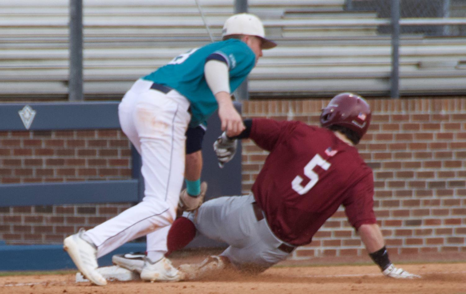 Cole Weiss (8) tags out Liam Bendo (5) during UNCW's season opener against St. Joseph on Feb. 15, 2019 at Brooks Field.