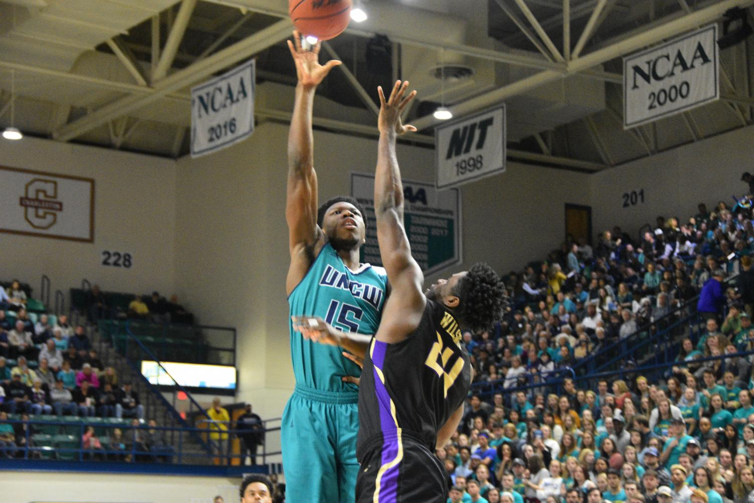 Devontae Cacok (15) hits a hook shot during UNCW's Homecoming matchup against James Madison on Feb. 2, 2019.