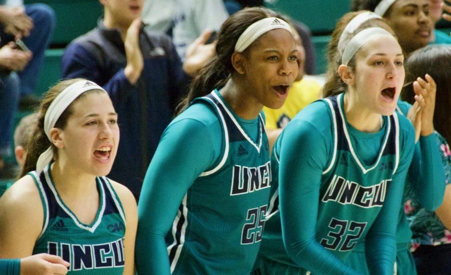 The Seahawk bench (from left: Grace Sacco, Micah Hoggatt and Carol-Anne Obusek) celebrates following a big play during UNCW's contest against Northeastern on Feb. 3, 2019.