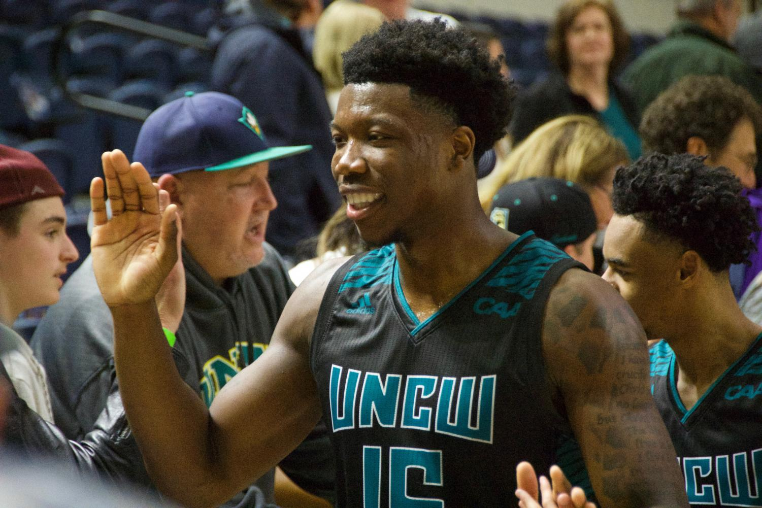 Devontae Cacok (15) celebrates with fans following UNCW's 87-79 Senior Night victory over Hofstra on Feb. 16, 2019.