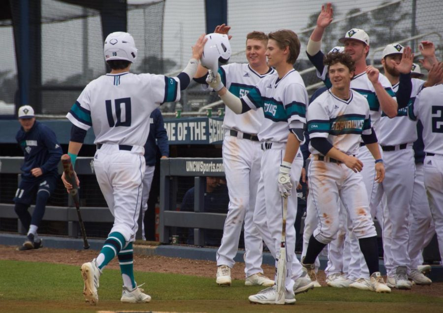 Brooks Baldwin (10) scores and is cheered on by his teammates following a 2 RBI double by Zachary Bridges during UNCW's game against Iona at Brooks Field on Feb. 23, 2019.