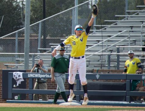 Brooks Baldwin (10) leaps for a ball thrown his way during UNCW's game against William & Mary on March 30, 2019 at Brooks Stadium.
