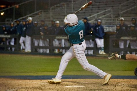 Cole Weiss (8) hits during UNCW's matchup against Toledo on Wednesday night at Brooks Field.