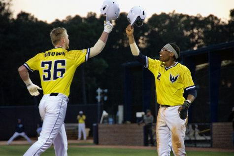 Kep Brown (36) and Greg Jones (2) celebrate following Brown's RBI homer during UNCW's matchup against Coastal Carolina at Brooks Field on March 26, 2019.