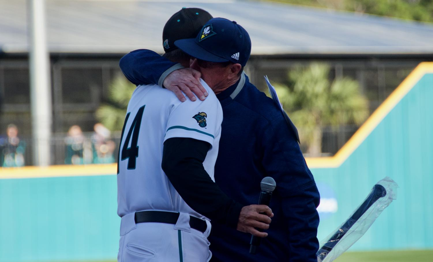 UNCW head coach Mark Scalf and Coastal Carolina head coach Gary Gilmore share a hug before Scalf's final matchup with the Chanticleers on March 27, 2019 at Springs Brooks Stadium.