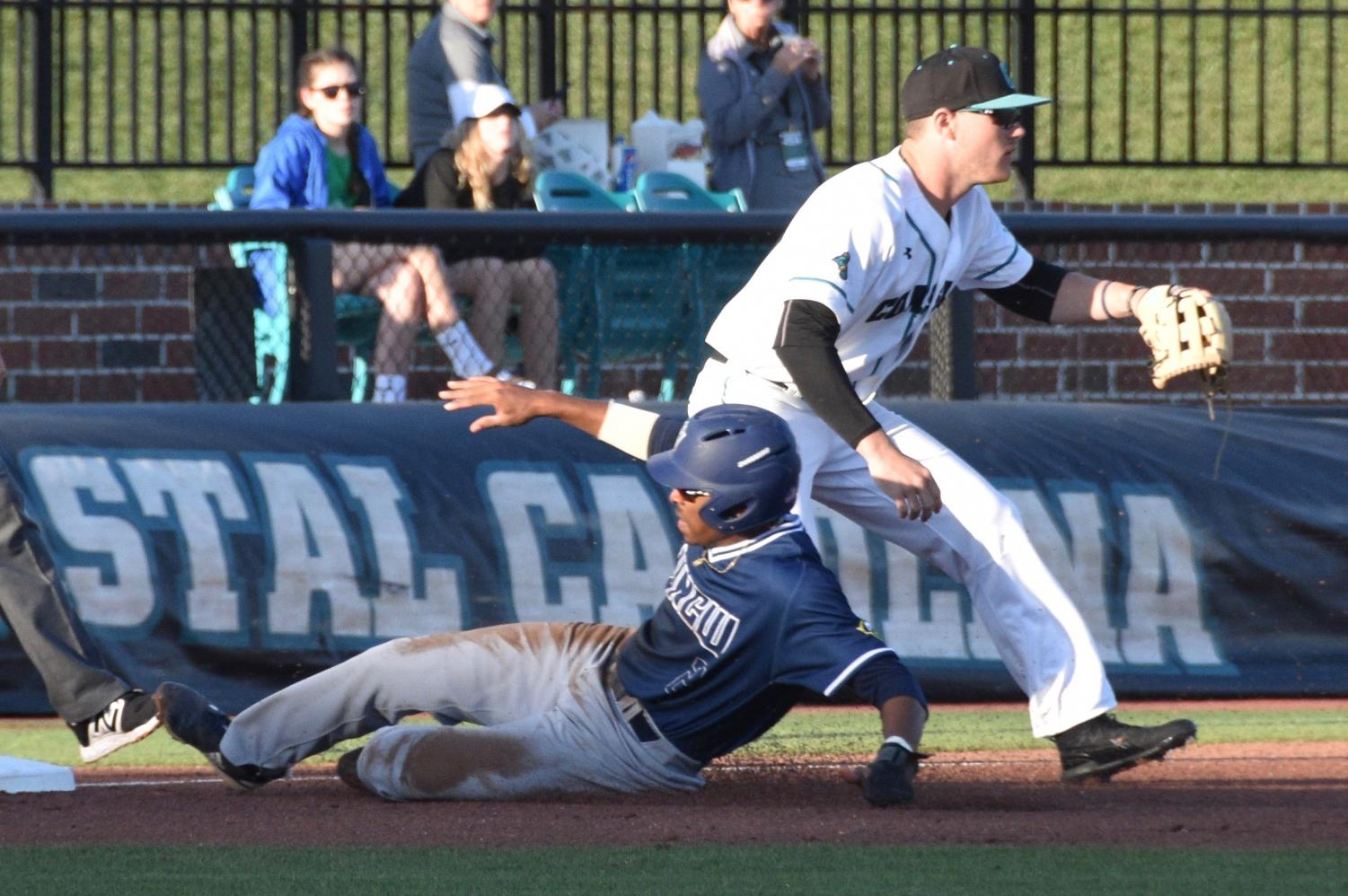 Greg Jones (2) slides into third base during UNCW's matchup against Coastal Carolina at Springs Brooks Stadium on March 27, 2019.