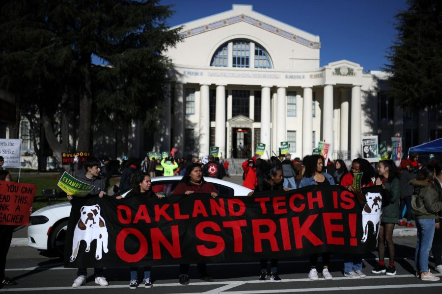 Oakland Unified School District students and teachers carry signs as they picket outside of Oakland Technical High School on February 21, 2019 in Oakland, California. Nearly 3,000 teachers in Oakland have gone on strike and are demanding a 12 percent retroactive raise.