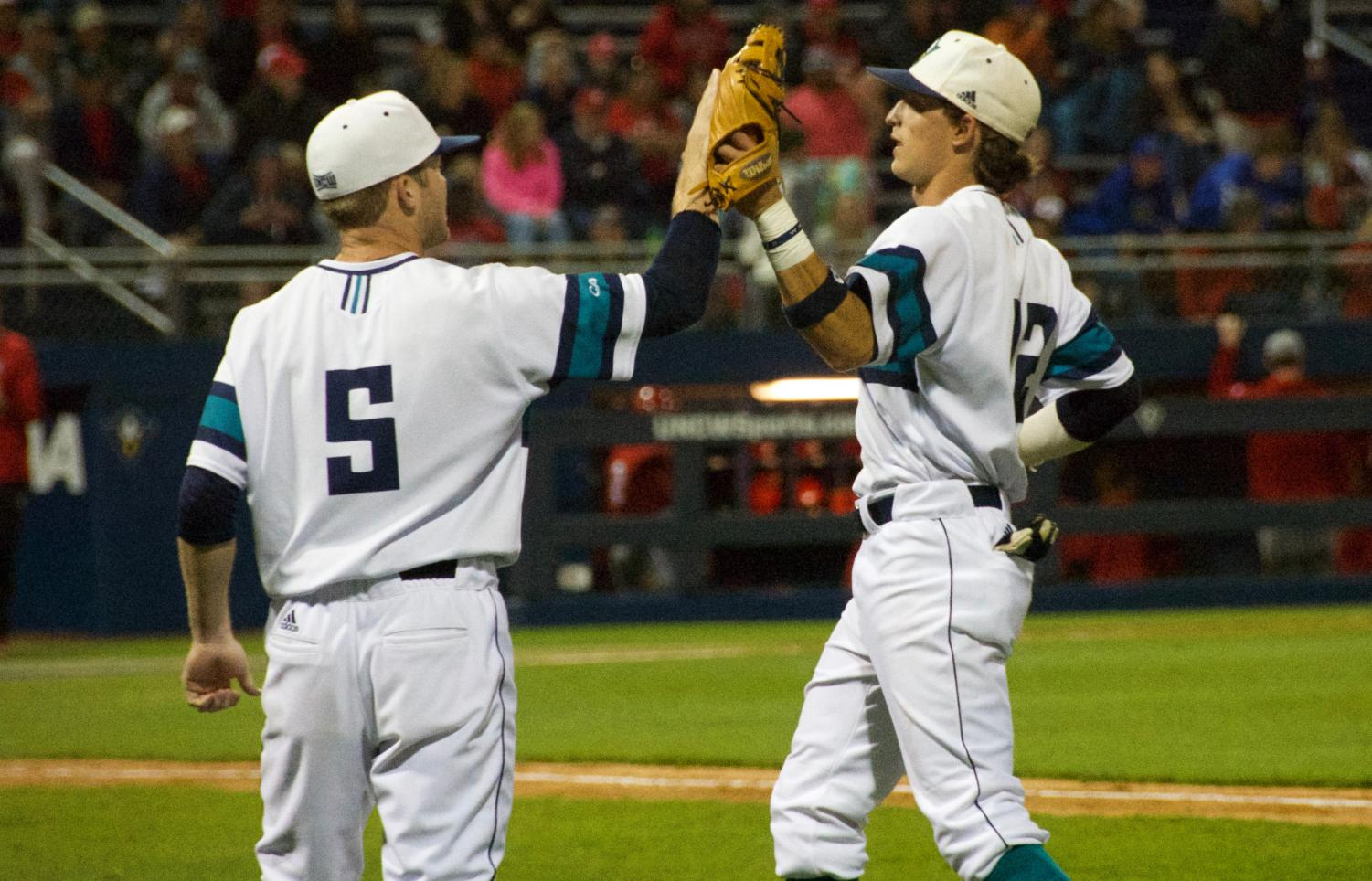 Noah Liles (5) high-fives Noah Bridges (22) during UNCW's contest against N.C. State at Brooks Field on April 16, 2019.