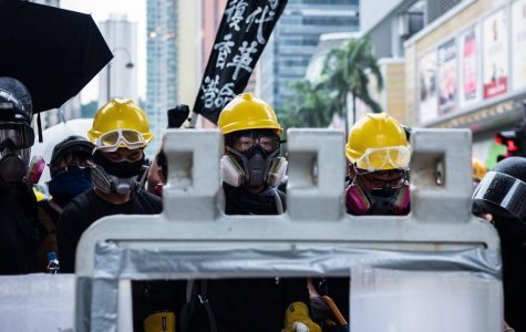 Protesters gaze at riot police from behind a barricade during a demonstration on Sunday, Aug. 25, 2019 in Hong Kong.