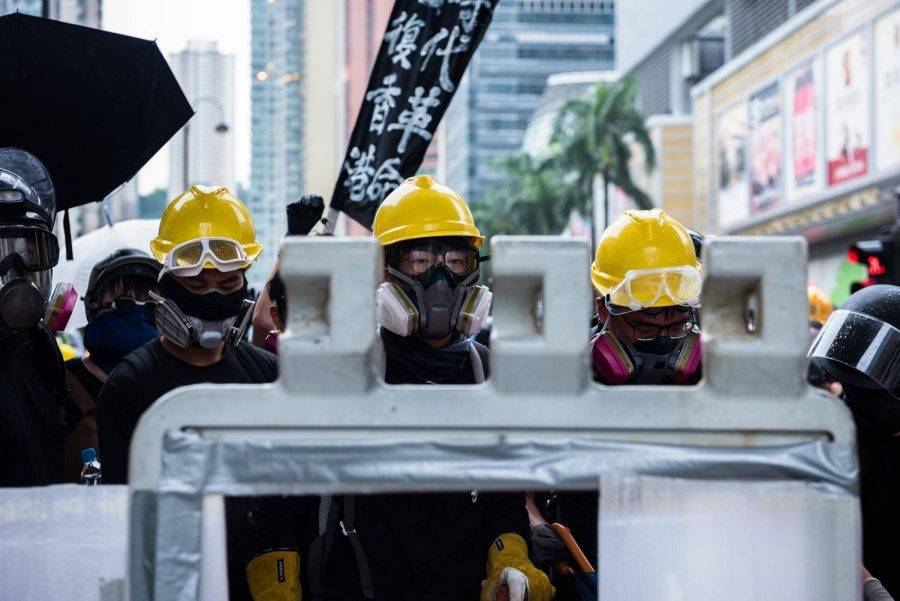 Protesters+gaze+at+riot+police+from+behind+a+barricade+during+a+demonstration+on+Sunday%2C+Aug.+25%2C+2019+in+Hong+Kong.
