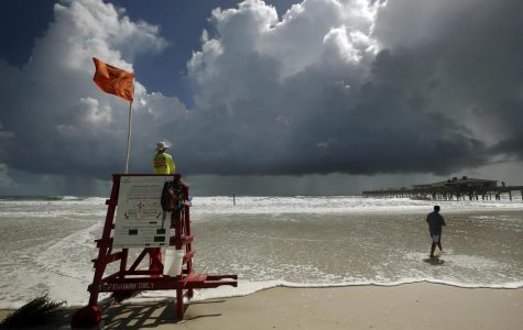 A lifeguard stand on a beach flying the emergency red flag, set against a dark sky in Daytona, FL.