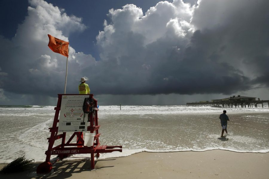 A+lifeguard+stand+on+a+beach+flying+the+emergency+red+flag%2C+set+against+a+dark+sky+in+Daytona%2C+FL.