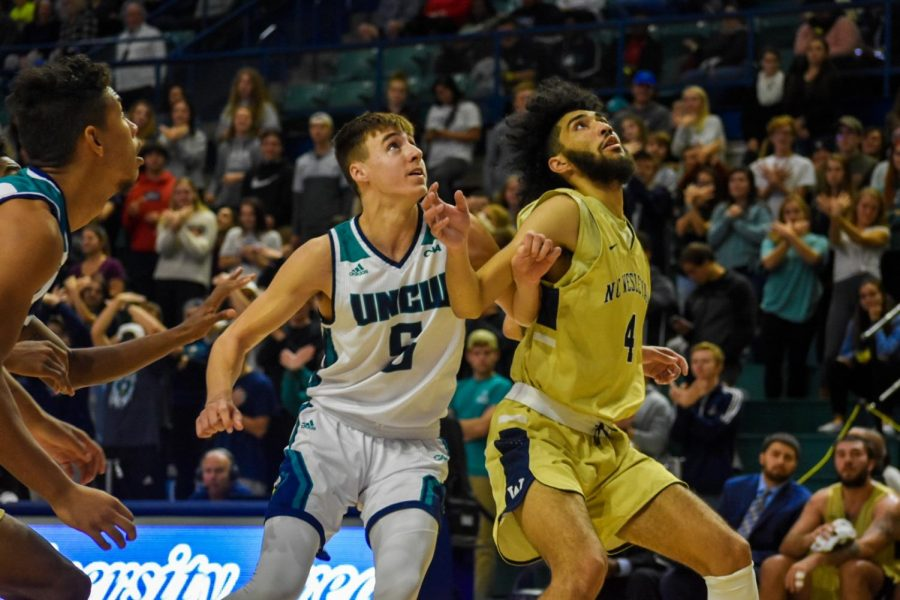 Jake Boggs attempts to grab a rebound during UNCW's matchup with N.C. Wesleyan on Nov. 19, 2019.
