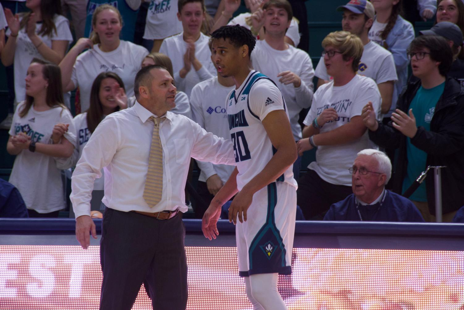 UNCW interim head coach Rob Burke talks to Jaylen Sims on the sideline during the Seahawks' matchup with Hofstra on Jan. 16, 2020