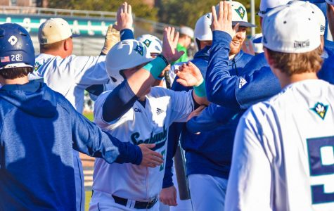 Tanner Wells (51) celebrates with the team after coming across home plate during UNCW's matchup with Marshall on Feb. 22, 2020 at Brooks Field.