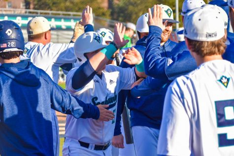 Tanner Wells (51) celebrates with the team after coming across home plate during UNCW